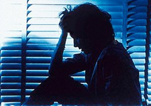 AFP6E1 Silhouette of a woman sitting by a window in a dim room and holding her head